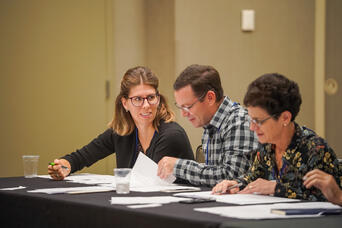 Conference attendees talk while reading papers