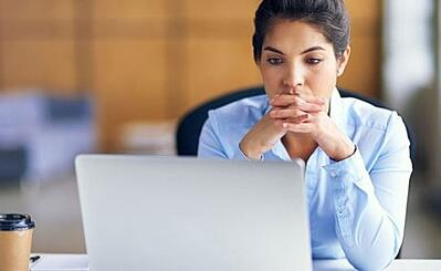 Woman looks at computer with hands folded